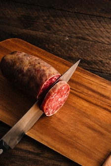 Knife cutting smoked sausage