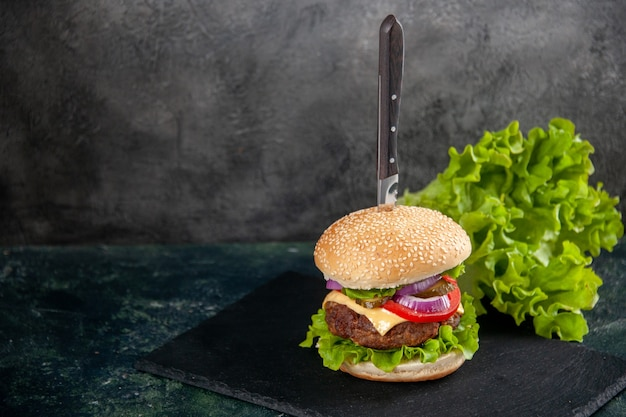 Knife in delicious meat sandwich and green on black tray on the left side on blurred surface with free space