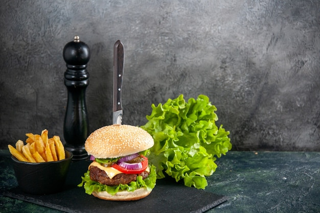 Knife in delicious meat sandwich and green fries pepper on black tray on isolated gray surface
