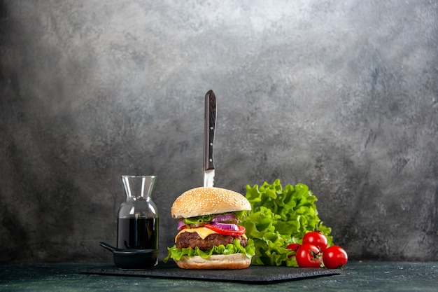 Coltello in delizioso panino di carne e pepe verde su salsa di vassoio nero su superficie grigia