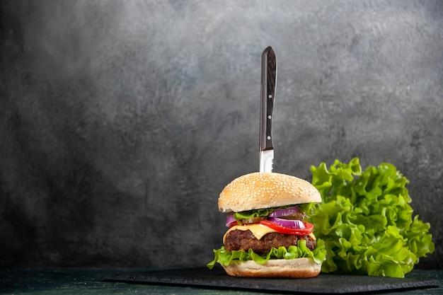Coltello in delizioso panino e verde su vassoio nero sul lato sinistro su mezza superficie chiara scura con spazio libero