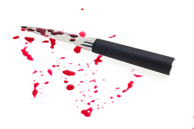 Knife and a drop of blood on white background.