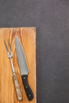 Knife and fork against wooden table
