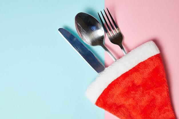 Нож, вилка и ложка в новогодней шапке на розовом и синем фоне с копией пространства