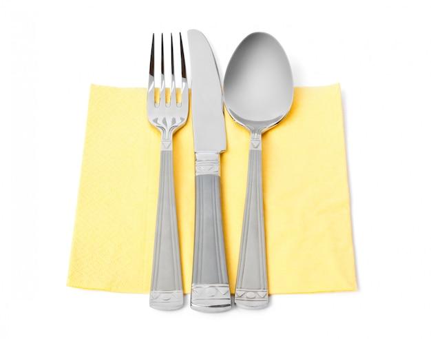 Нож, вилка и ложка на салфетке, изолированные на белом