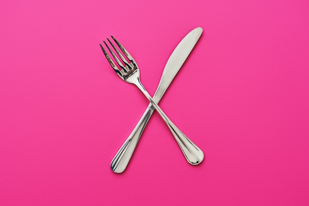 Knife and fork crossed isolated on pink background