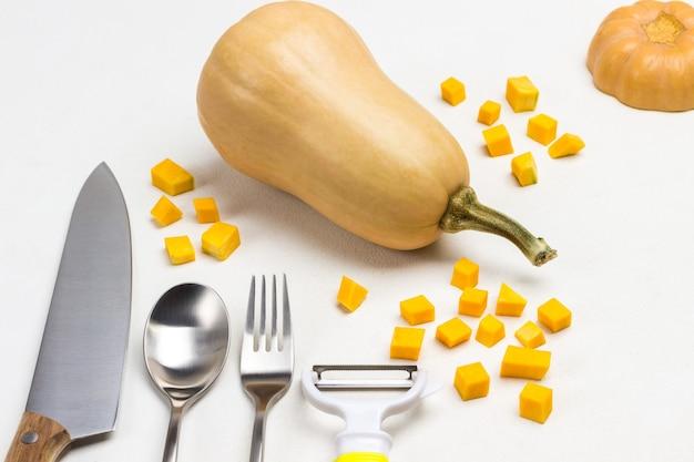 テーブルの上のナイフ、フォーク、スプーン、皮むき器、スライスしたカボチャの部分。乾燥した茎を持つ全体のカボチャ。上面図。白色の背景