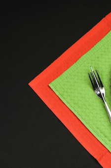 Knife and fork with christmas decoration for holiday menu on black background