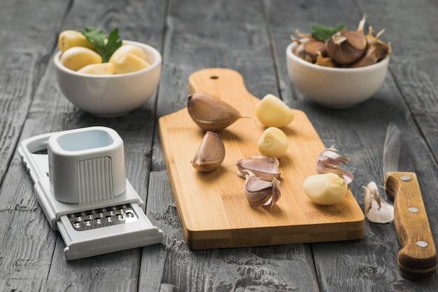 木製のテーブルのまな板にナイフ、おろし金、ディルのスライス。キッチンに人気のスパイス。