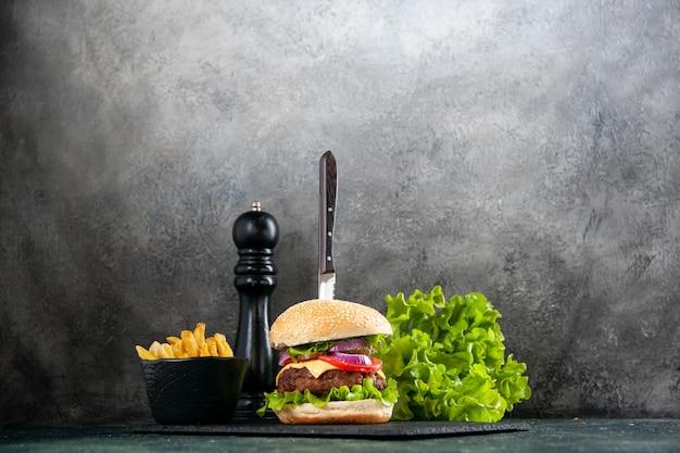 어두운 빛 표면에 검은 쟁반에 맛있는 고기 샌드위치와 녹색 감자 튀김에 칼