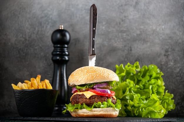 회색 표면에 검은 쟁반에 맛있는 고기 샌드위치와 녹색 감자 튀김 칼