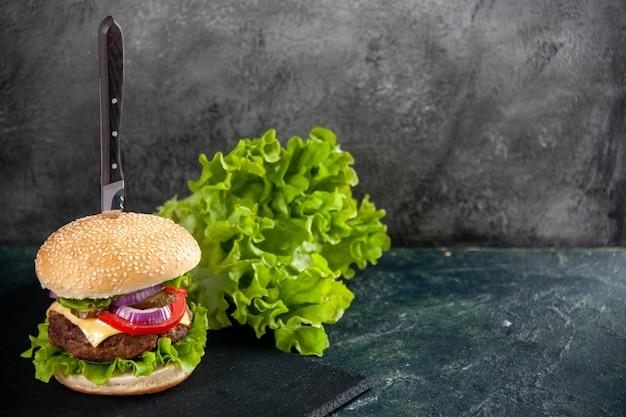 맛있는 고기 샌드위치의 칼과 여유 공간이있는 반 어두운 밝은 표면의 검은 색 트레이 오른쪽에 녹색