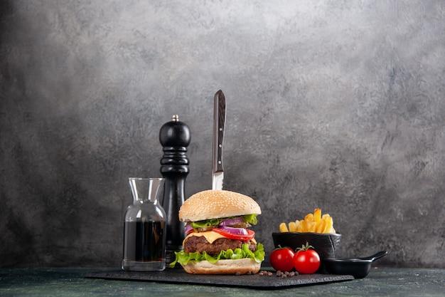 Нож в вкусном мясном сэндвиче и зеленом перце на черном подносе, соус кетчуп, помидоры с картофелем фри на серой поверхности