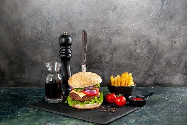 격리 된 어두운 표면에 줄기 튀김과 검은 트레이 소스 케첩 토마토에 맛있는 고기 샌드위치와 피망에 칼