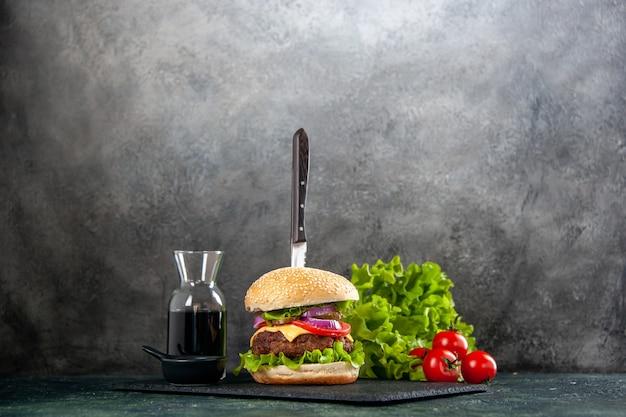Нож в вкусном мясном сэндвиче и зеленом перце на черном соусе на подносе на серой поверхности