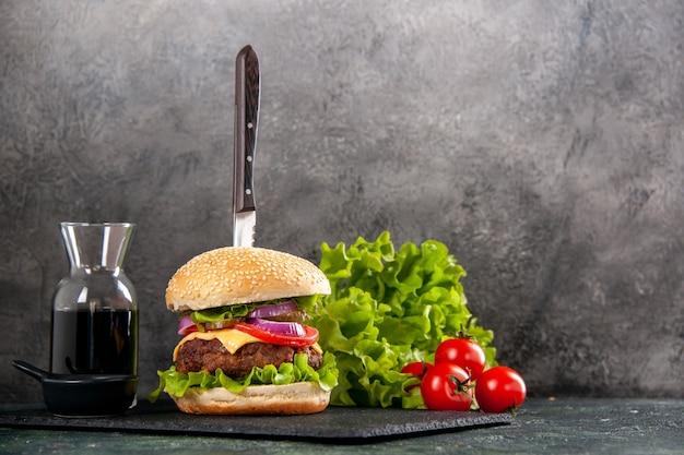 Нож в вкусном мясном сэндвиче и зеленом перце на черном соусе из помидоров со стеблем с правой стороны на серой поверхности