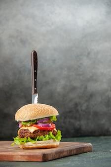 孤立した暗い表面に木製のまな板の上のおいしい肉サンドイッチのナイフ