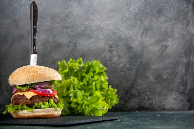 맛있는 샌드위치의 칼과 여유 공간이있는 반 어두운 빛 표면의 오른쪽에 검은 색 트레이에 녹색