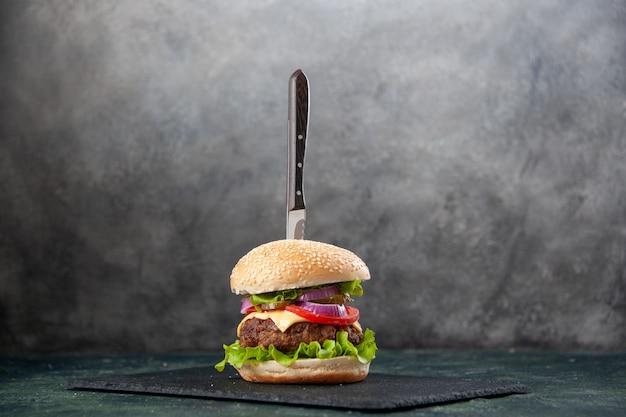 여유 공간이있는 고립 된 흐린 회색 표면에 검은 쟁반에 맛있는 샌드위치에 칼