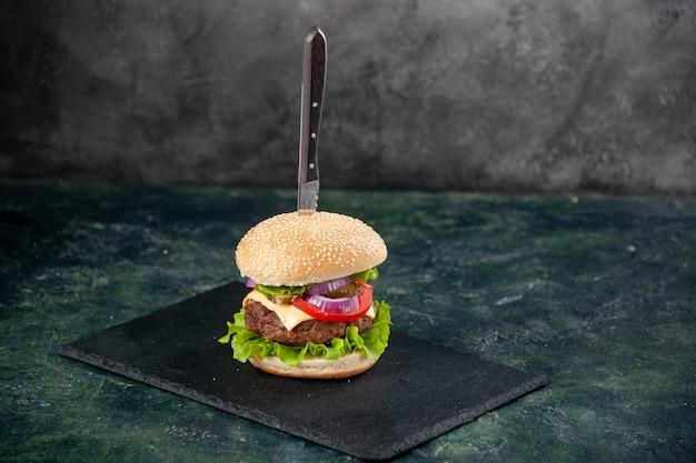 空きスペースのある孤立したぼやけた表面に黒いトレイにおいしいサンドイッチのナイフ