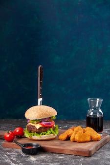 Нож в мясном бутерброде и куриные наггетсы, помидоры со стеблем на деревянной доске, соус кетчуп на темно-синей поверхности