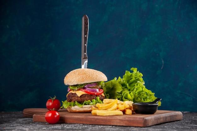 진한 파란색 표면에 나무 보드 케첩에 줄기와 고기 샌드위치와 감자 튀김 토마토 칼