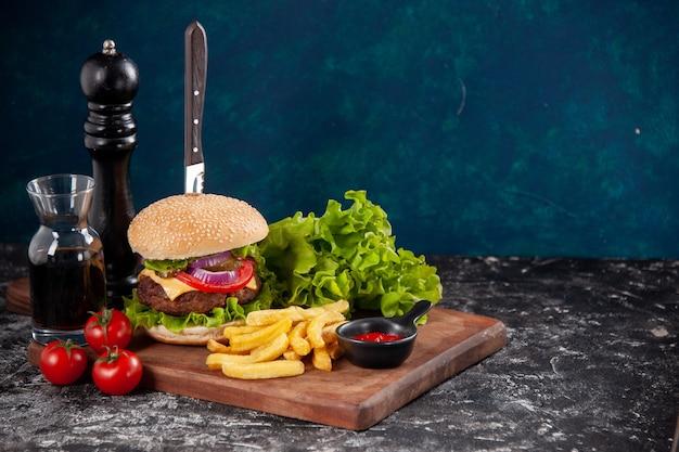 肉のサンドイッチとフライド ポテト トマトに木の板に茎を入れたナイフ ソース ケチャップを濃い青色の表面に