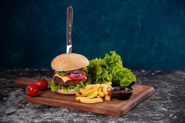 어두운 파란색 표면에 나무 보드 케첩에 줄기 고추와 고기 샌드위치와 감자 튀김 토마토 칼
