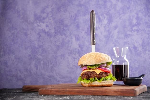 空きスペースのある孤立した氷の表面の左側にある木製のまな板に、おいしい肉サンドイッチ ソース ケチャップのナイフ
