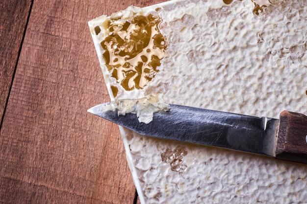 木製の背景に蜂蜜とハニカムのナイフ。