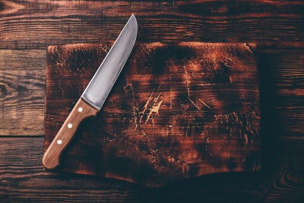素朴な木製のまな板の上にナイフ。上から見る