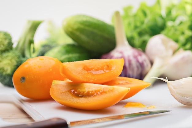 Нож, кусочки желтых помидоров, чеснок и другие ранние овощи.