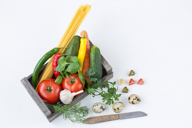 Knife, quail eggs, spaghetti and fresh vegetables in a wooden box on the table