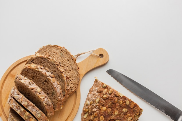 Knife and sliced of bread on wooden board