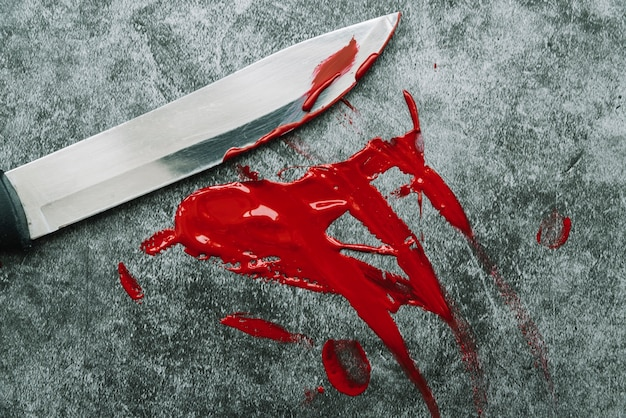 Knife and smeared out artificial blood on stone surface