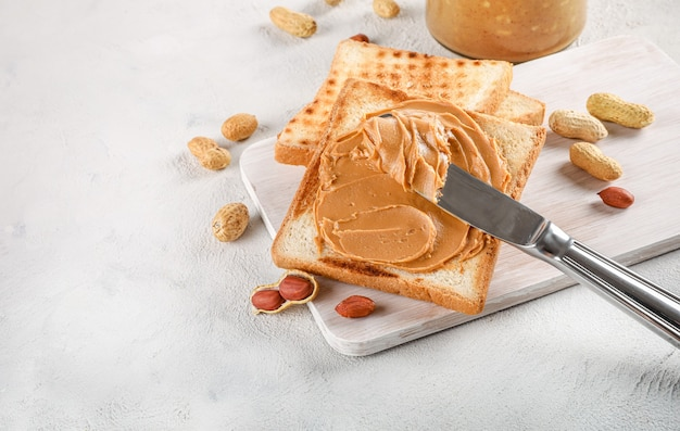 Knife spreading peanut butter on toast bread on white