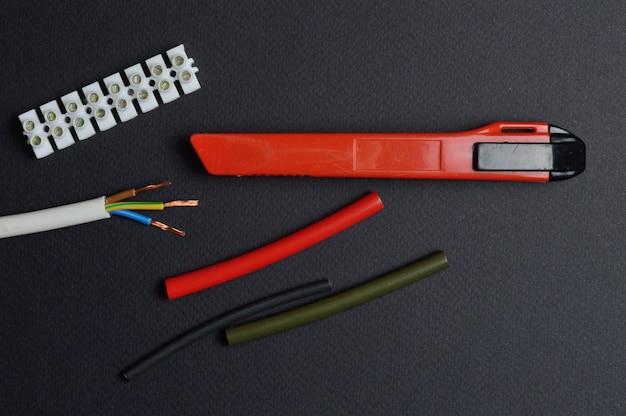 ナイフ、端子台付きの剥き線、および熱収縮チューブが暗い背景にあります。上からの眺め。