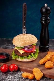 Coltello in gustoso sandwich di carne e pepite di pollo pomodori con pepe a gambo su tavola di legno salsa ketchup su superficie blu scuro