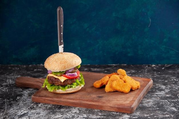 Coltello in gustoso panino di carne e bocconcini di pollo su tagliere di legno su superficie blu scuro
