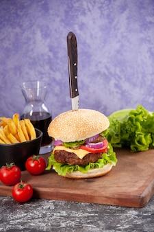 Coltello in gustoso sandwich di carne con salsa ketchup e patatine fritte su tavola di legno e pomodori con gambo su superficie di ghiaccio isolata