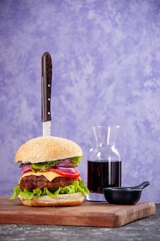 Coltello in gustoso ketchup di salsa di sandwich di carne su tagliere di legno su superficie di ghiaccio isolata con spazio libero free