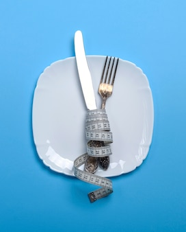 Knife with a fork wrapped in a measuring tape with  ceramic plate