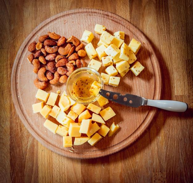 暗いテーブルのチーズの部分とナイフ