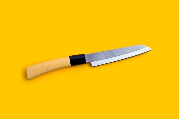 A knife on yellow background. copy space