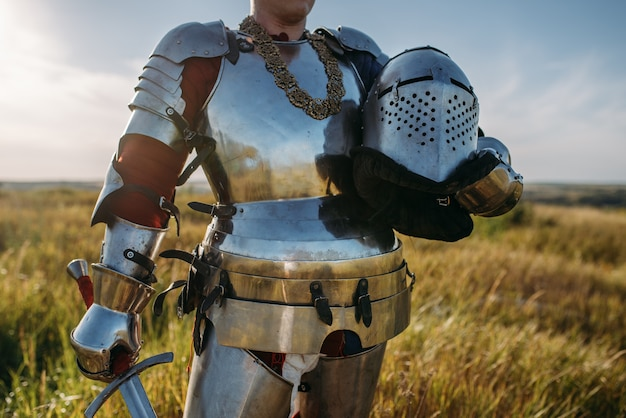 Knight in armor and helmet holds sword. armored ancient warrior in armour posing in the field