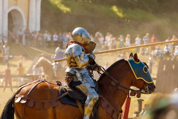 Рыцарь в средневековых доспехах верхом на коне. фото высокого качества