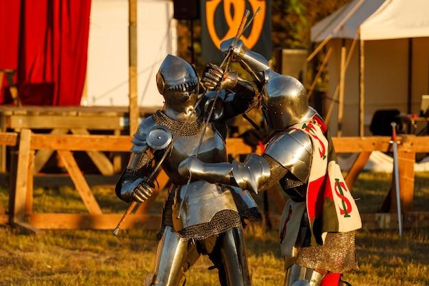 Летом на турнире сражаются рыцари в средневековых доспехах. фото высокого качества