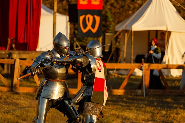 Knights in medieval armor fight at the tournament in the summer. high quality photo