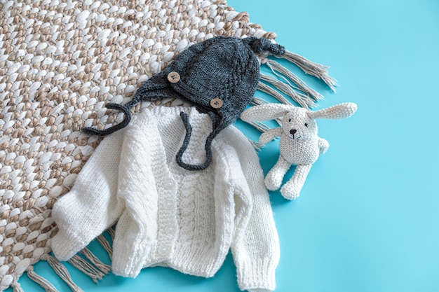 Knitted baby clothes and accessories on blue