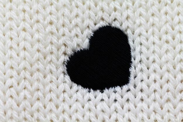 Вязаный фон белого цвета с черным сердцем на нем